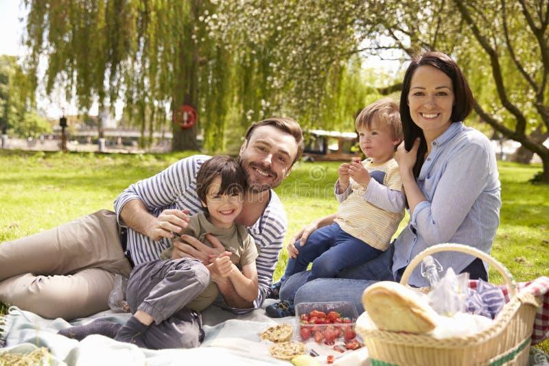 Familia que disfruta de comida campestre de la orilla junto foto de archivo