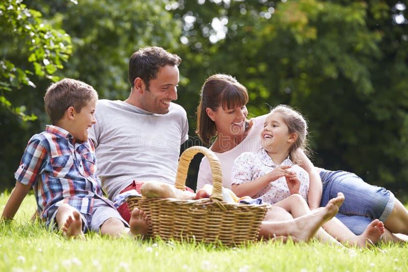 Familia que disfruta de comida campestre del verano en campo imagenes de archivo