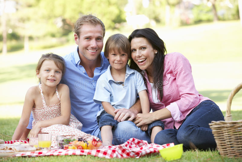 Familia que disfruta de comida campestre junto imagen de archivo libre de regalías