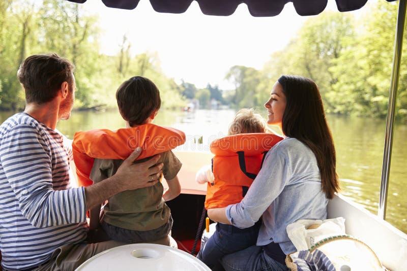 Familia que disfruta de día hacia fuera en barco en el río junto fotos de archivo