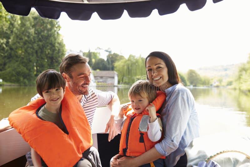 Familia que disfruta de día hacia fuera en barco en el río junto imagenes de archivo