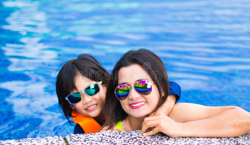 Familia que disfruta de vacaciones de verano en piscina de lujo fotografía de archivo