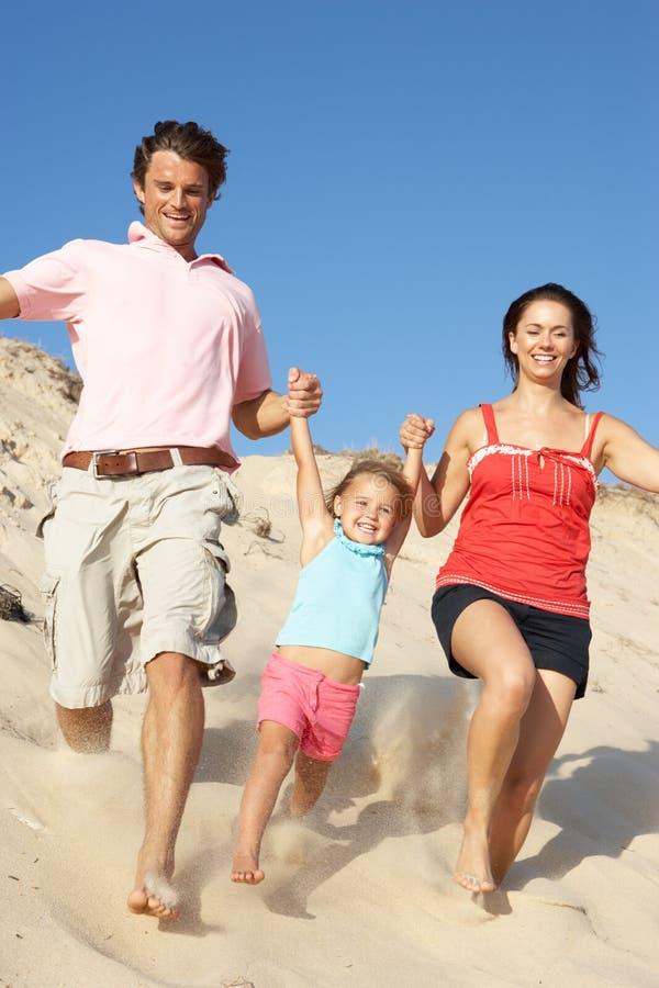 Familia que disfruta del día de fiesta de la playa que se ejecuta abajo de la duna fotografía de archivo libre de regalías