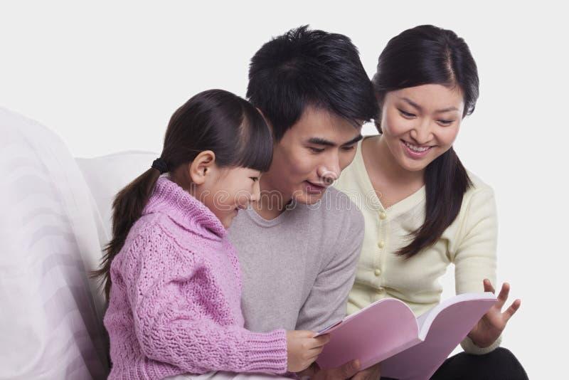Familia que enlaza junto, sonriendo y leyendo en el sofá, tiro del estudio imagen de archivo
