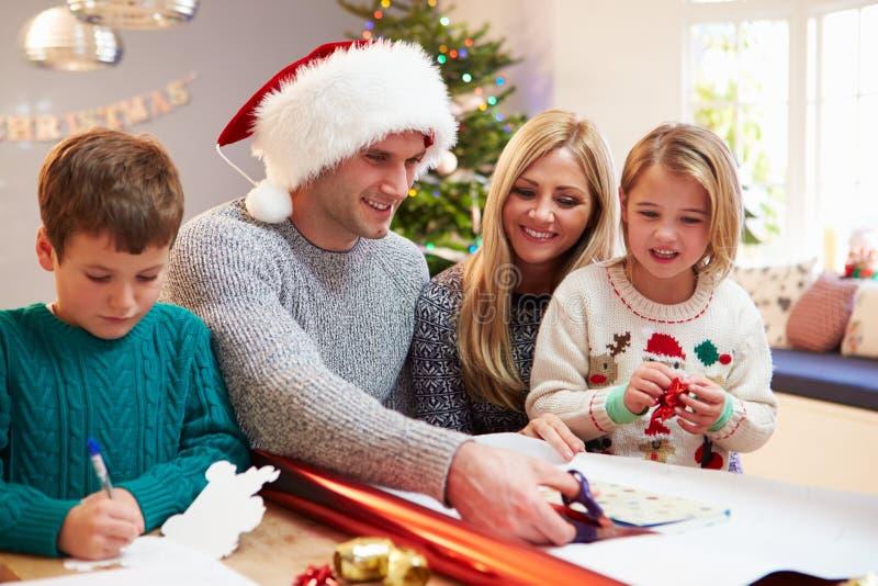 Familia que envuelve los regalos de la Navidad en casa imagen de archivo libre de regalías