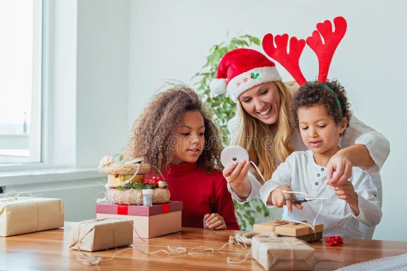 Familia que envuelve regalos de Navidad en la tabla fotos de archivo