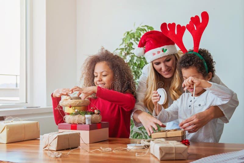Familia que envuelve regalos de Navidad en la tabla fotografía de archivo