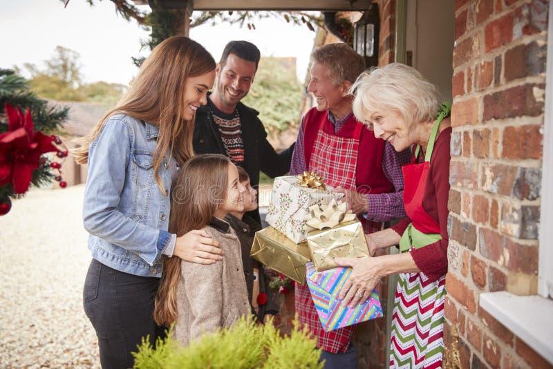 Familia que es saludada por los abuelos como llegan para la visita el día de la Navidad con los regalos imagen de archivo libre de regalías