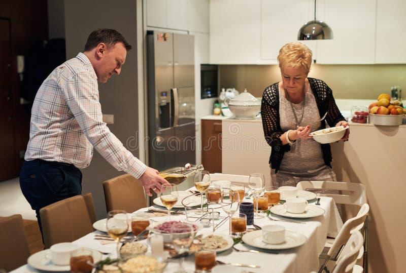 Familia que fija la mesa de comedor junto para la cena de la Navidad foto de archivo