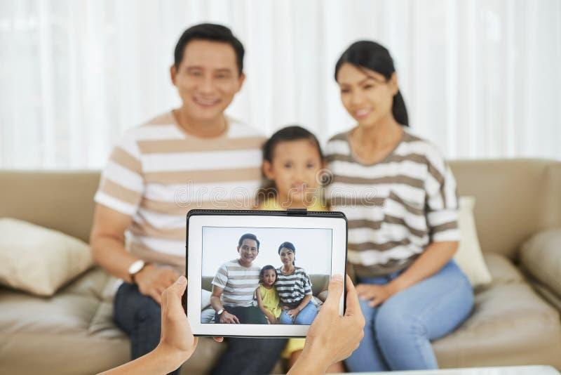 Familia que fotografía en casa imagenes de archivo