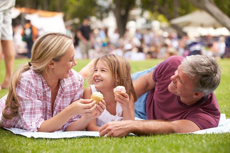 Familia que goza de las magdalenas en el evento al aire libre del verano fotografía de archivo libre de regalías