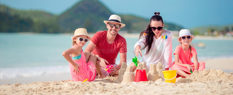 Familia que hace el castillo de la arena en la playa tropical foto de archivo