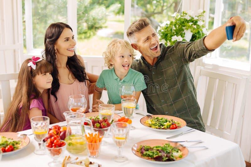 Familia que hace el selfie mientras que almorzando en casa de verano imagen de archivo