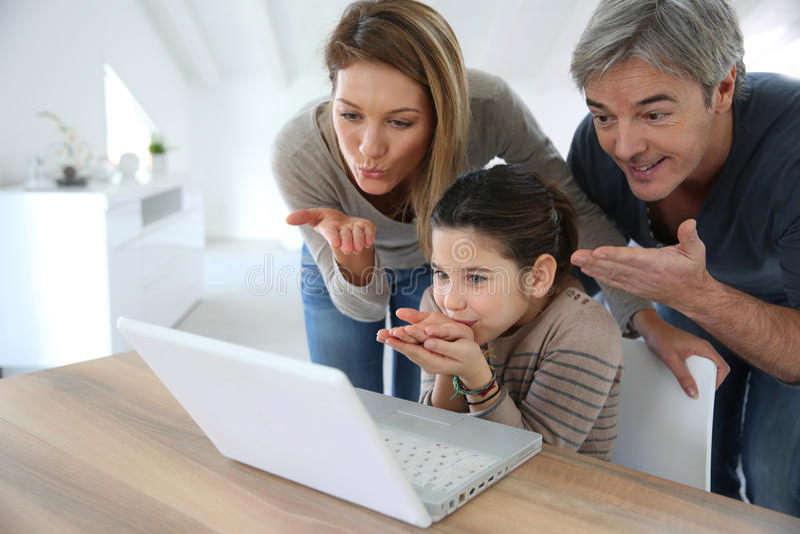 Familia que hace una llamada video en el ordenador portátil fotografía de archivo