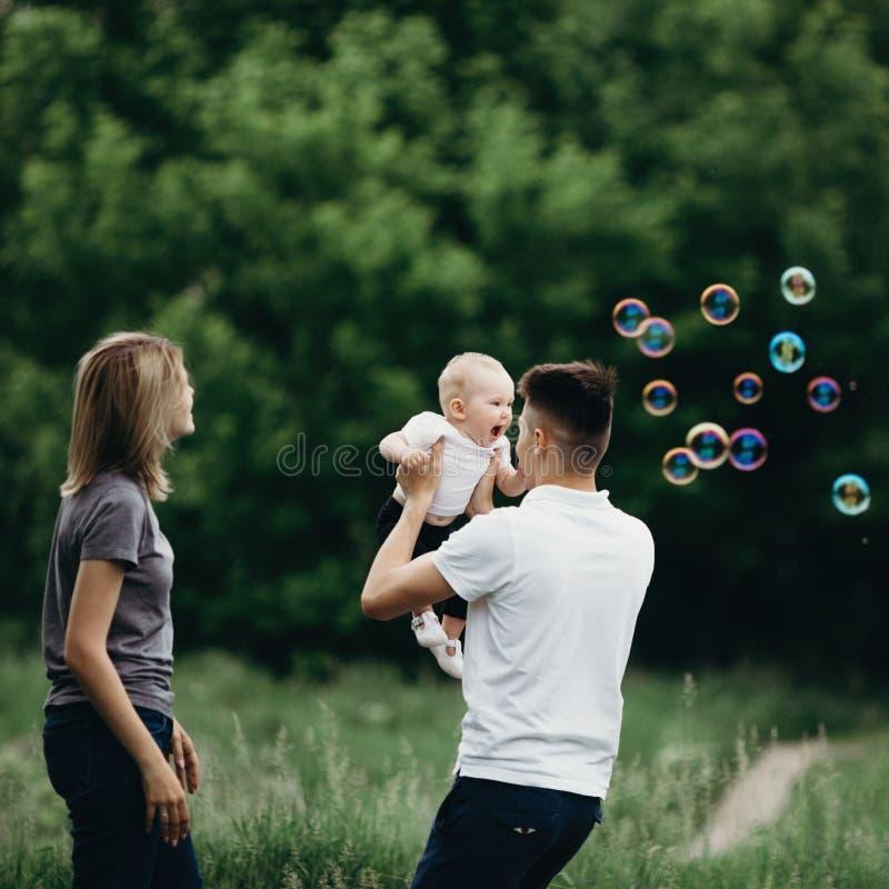 Familia que juega al aire libre, burbujas de jabón que soplan imagen de archivo
