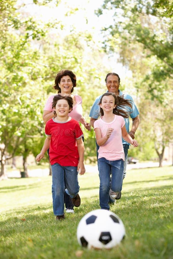 Familia que juega al balompié en parque imagenes de archivo