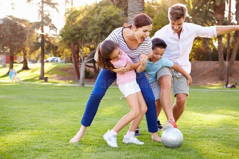 Familia que juega al fútbol en parque junto fotografía de archivo libre de regalías