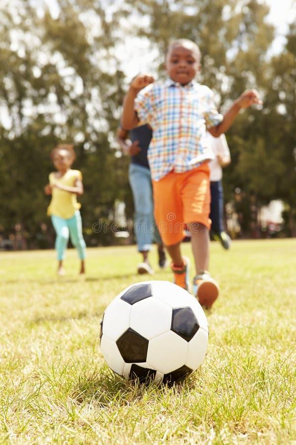 Familia que juega al fútbol en parque junto fotos de archivo
