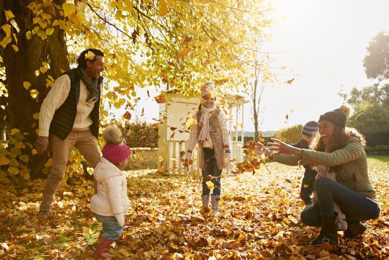 Familia que juega con Autumn Leaves In Garden Together imagenes de archivo