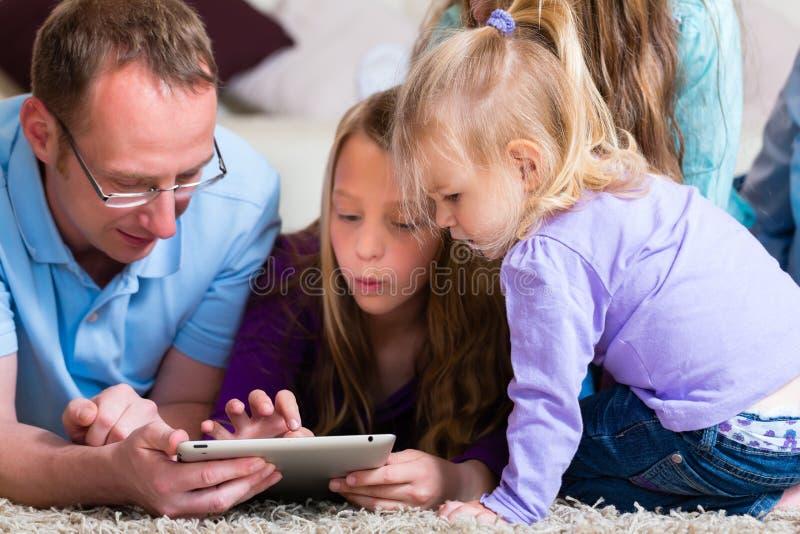 Familia que juega con el ordenador de la tablilla en el país imagenes de archivo