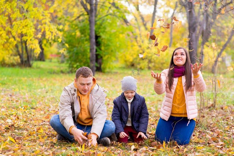 Familia que juega con el parque del otoño de las hojas imagen de archivo libre de regalías
