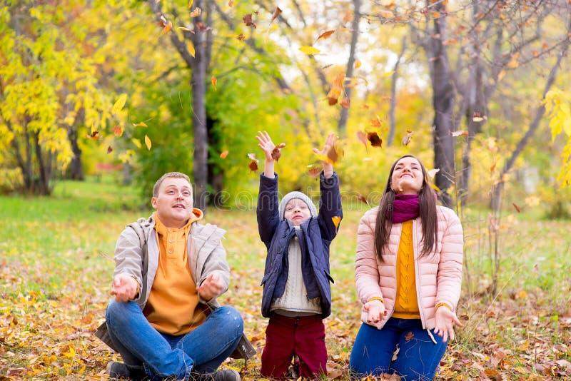 Familia que juega con el parque del otoño de las hojas foto de archivo