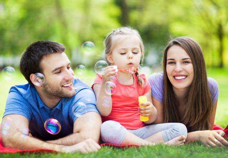 Familia que juega con las burbujas al aire libre imagen de archivo libre de regalías