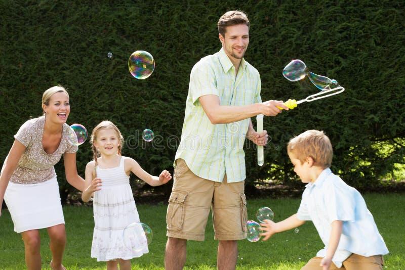 Familia que juega con las burbujas en jardín imagenes de archivo