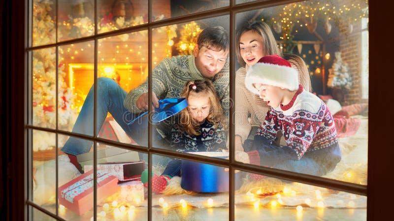 Familia que juega con los regalos dentro el día de la Navidad imagenes de archivo