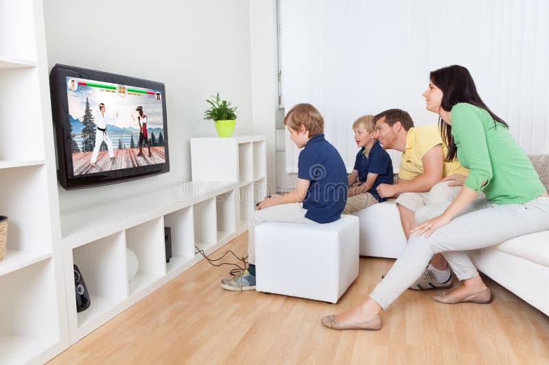 Familia que juega el videojuego en la televisión fotos de archivo libres de regalías
