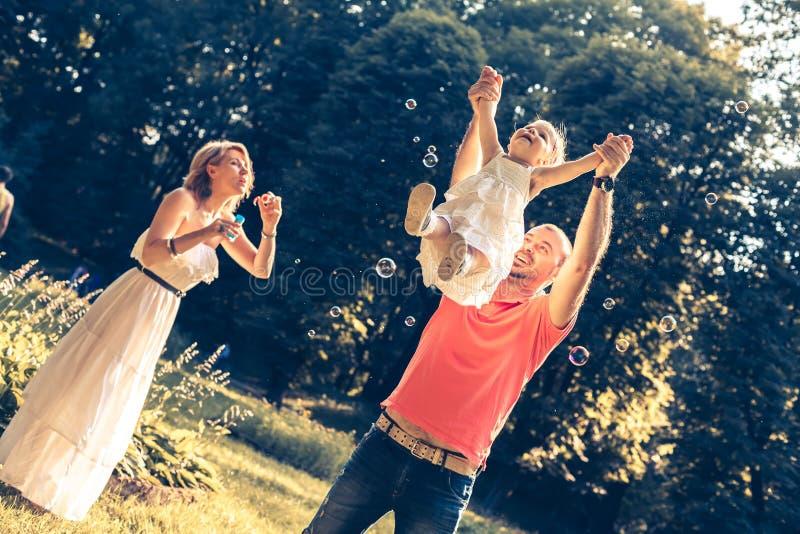 Familia que juega en el parque imagenes de archivo