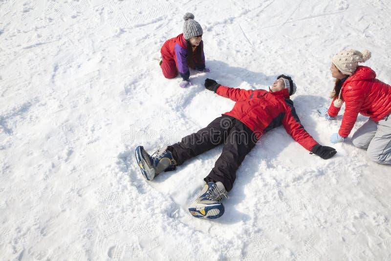 Familia que juega en la nieve, padre Making Snow Angel fotos de archivo libres de regalías