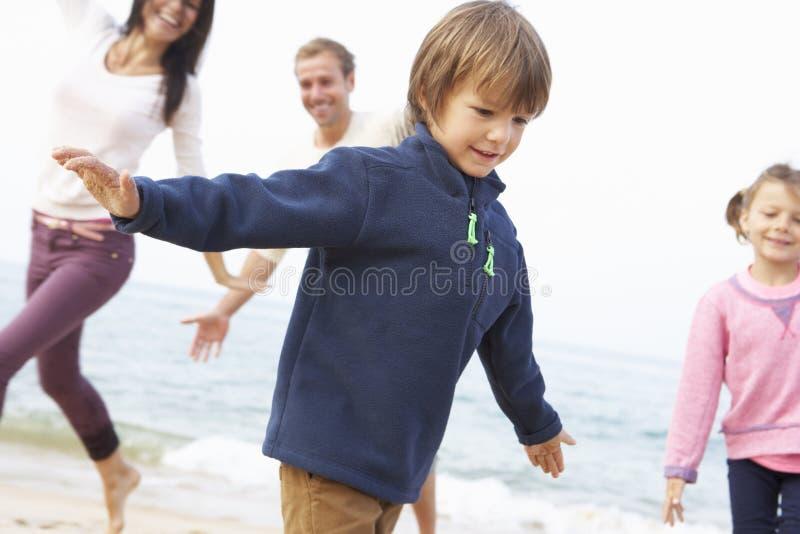 Familia que juega en la playa junto imagen de archivo