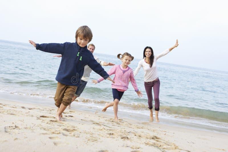 Familia que juega en la playa junto imagen de archivo libre de regalías