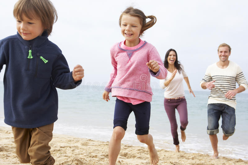 Familia que juega en la playa junto imágenes de archivo libres de regalías