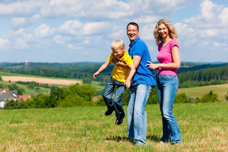 Familia que juega en prado en verano fotografía de archivo