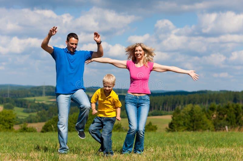 Familia que juega en prado en verano foto de archivo