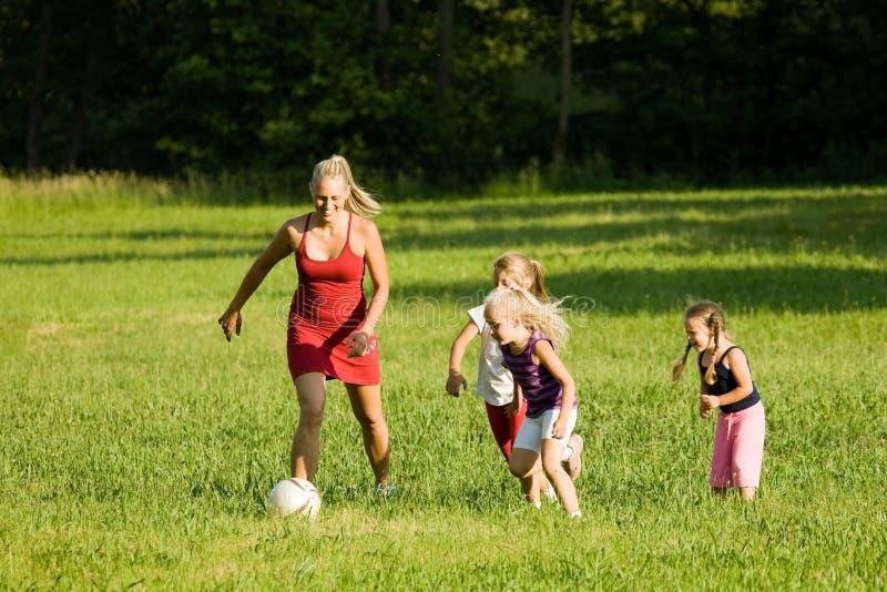 Familia que juega a fútbol foto de archivo libre de regalías