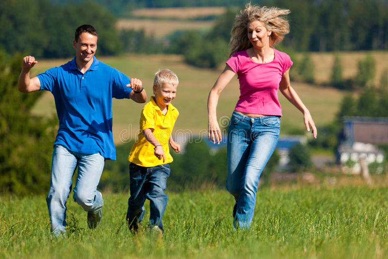 Familia que juega la etiqueta en prado en verano foto de archivo libre de regalías