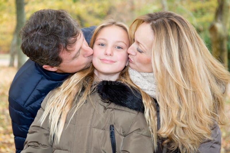 Familia que juega a la hija del beso rubia en parque del otoño foto de archivo