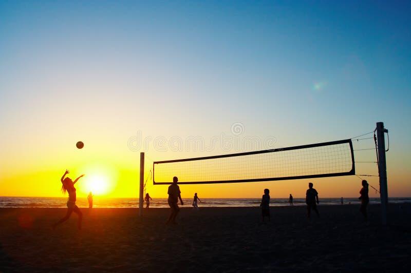 Familia que juega a voleibol de la playa foto de archivo