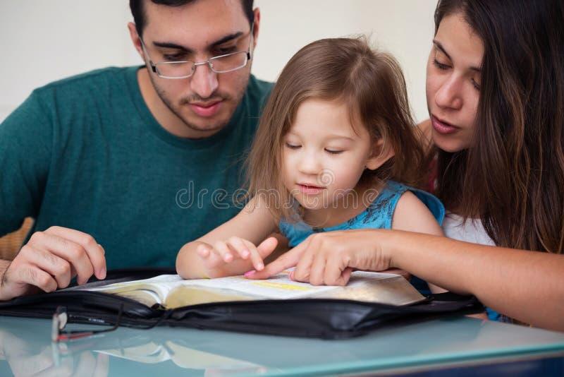 Familia que lee la biblia junto imagen de archivo