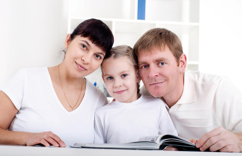 Familia que lee un libro junto fotos de archivo libres de regalías