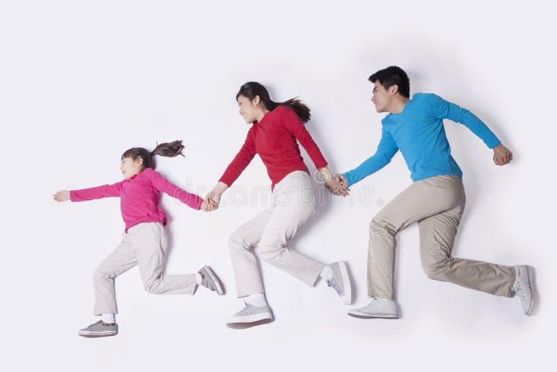 Familia que lleva a cabo de lado a lado las manos con las piernas y los brazos hacia fuera que corren, tiro del estudio fotografía de archivo