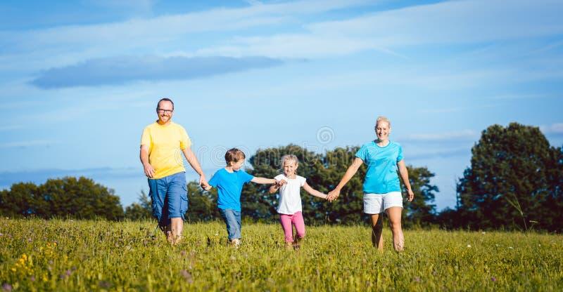 Familia que lleva a cabo las manos que corren sobre prado fotos de archivo