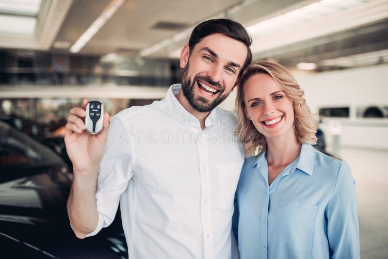 Familia que lleva a cabo llaves del nuevo coche fotografía de archivo libre de regalías