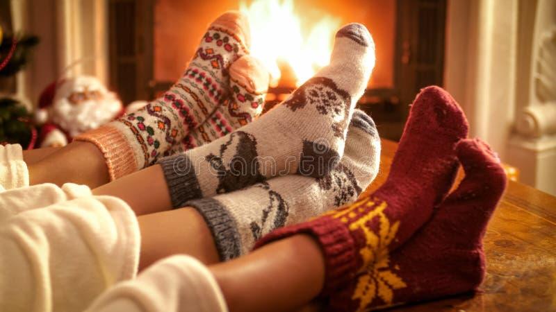 Familia que lleva los calcetines de lana hechos punto que calientan pies en la chimenea el Nochebuena imagen de archivo