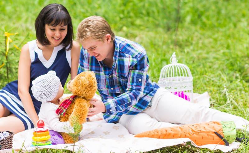Familia que merienda en el campo al aire libre con su hija linda fotos de archivo libres de regalías