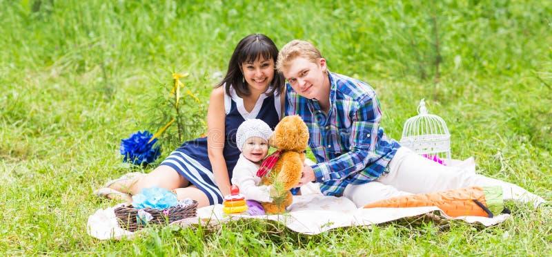Familia que merienda en el campo al aire libre con su hija linda imagenes de archivo