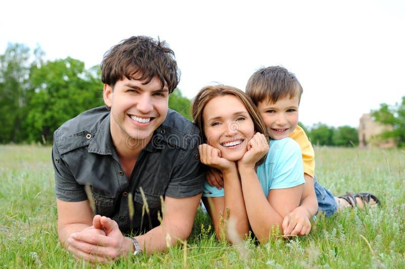 Familia que miente en la hierba verde foto de archivo